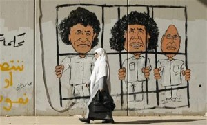 Woman walks past graffiti on wall of former Libyan leader Gaddafi, his son al-Islam Gaddafi and former head of Libyan Intelligence Service Al-Senussi in Tripoli